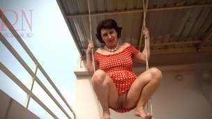 Depraved housewife waving on a swing outdoors